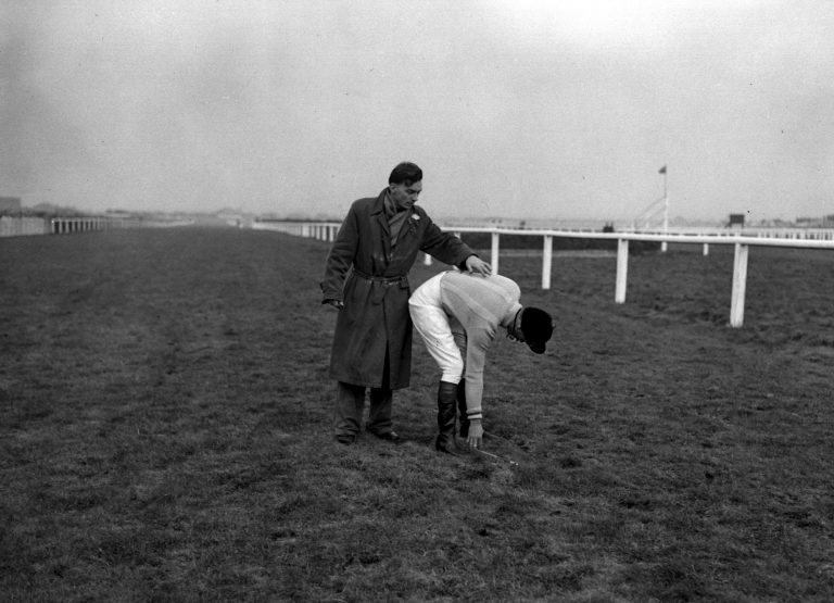 Dick Francis bends down to pick up his whip after Devon Loch's slip